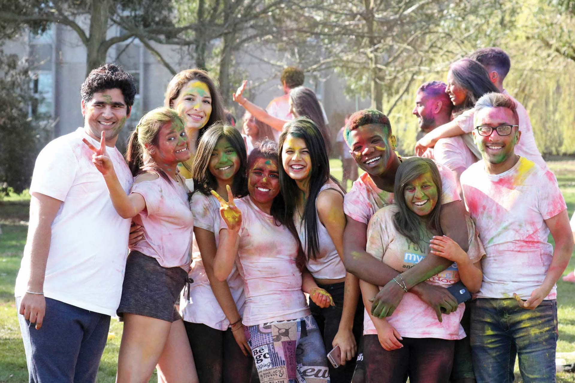 Paint-covered smiling students celebrating Holi