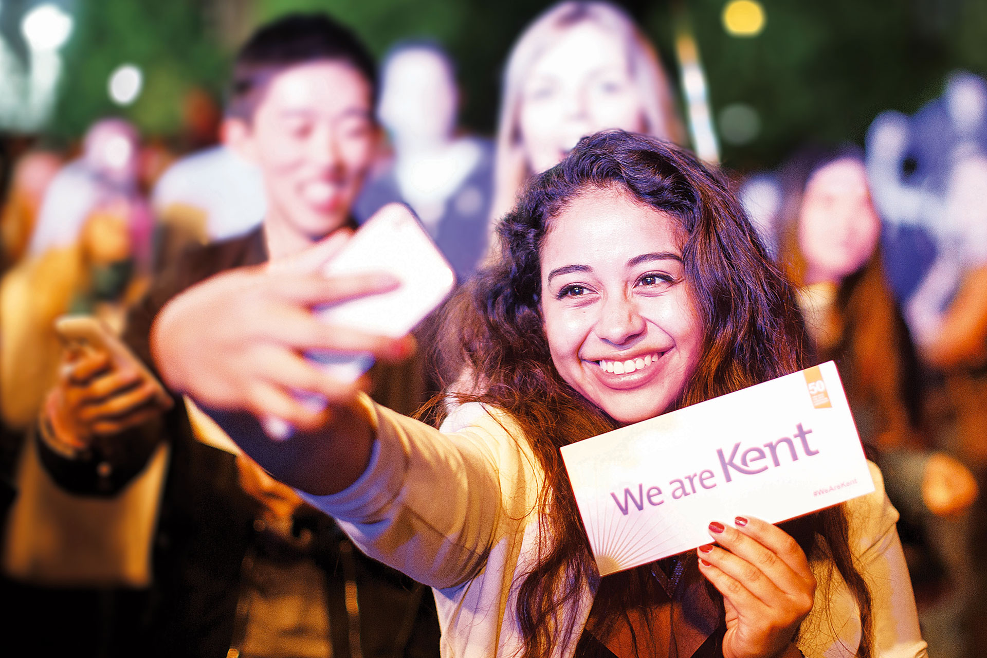 Student taking a selfie holding a We are Kent