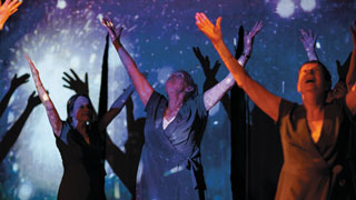 Several people standing with their arms raised, in front of a starry blue background. Light is projected onto them so their shadows appear on the background.